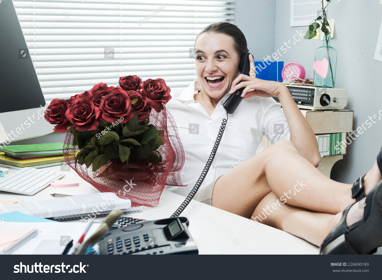 Frustrated office worker on the phone holding stock photo image - Female Office Worker Feet Up On Desk Talking On The Phone And Holding Roses
