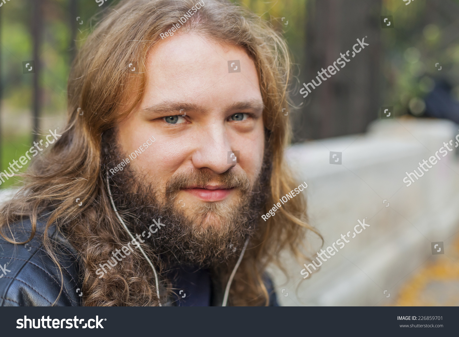 Blond Long Hair And Beard Young Adult Hipster Man Listening Music. Outdoor,  Urban Scene