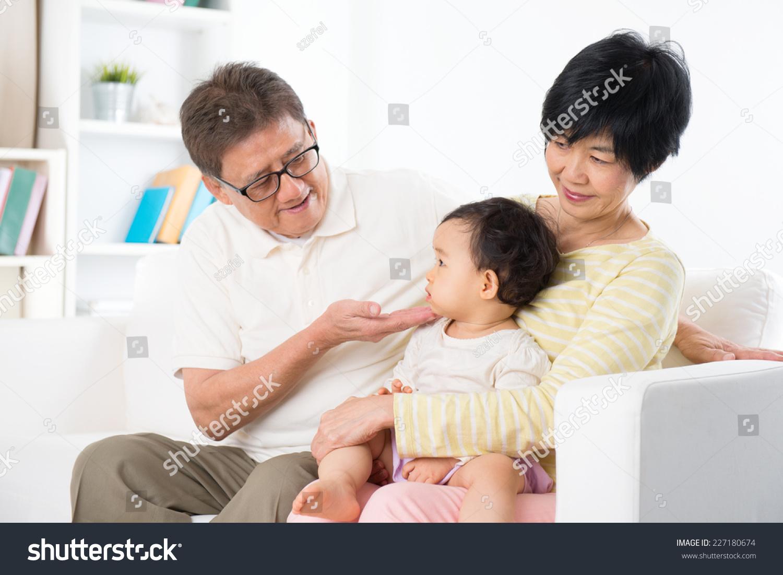 asian family relaxing indoor grandparents grandchild stock photo