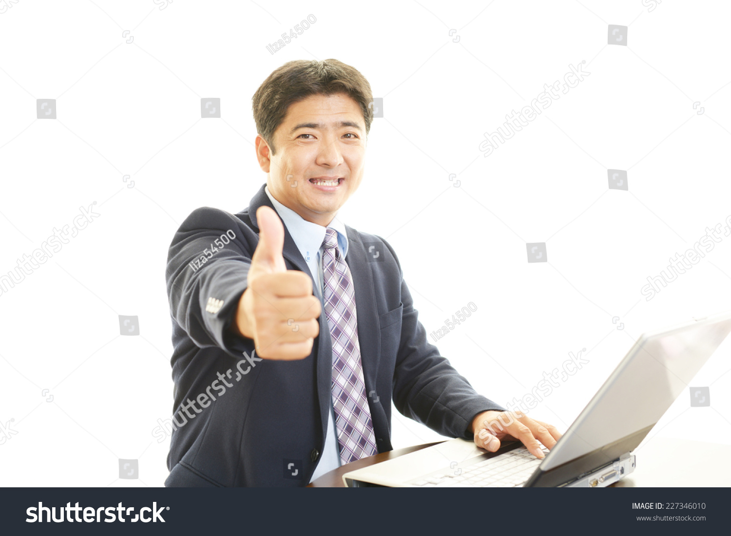 Smiling businessman using laptop #227346010