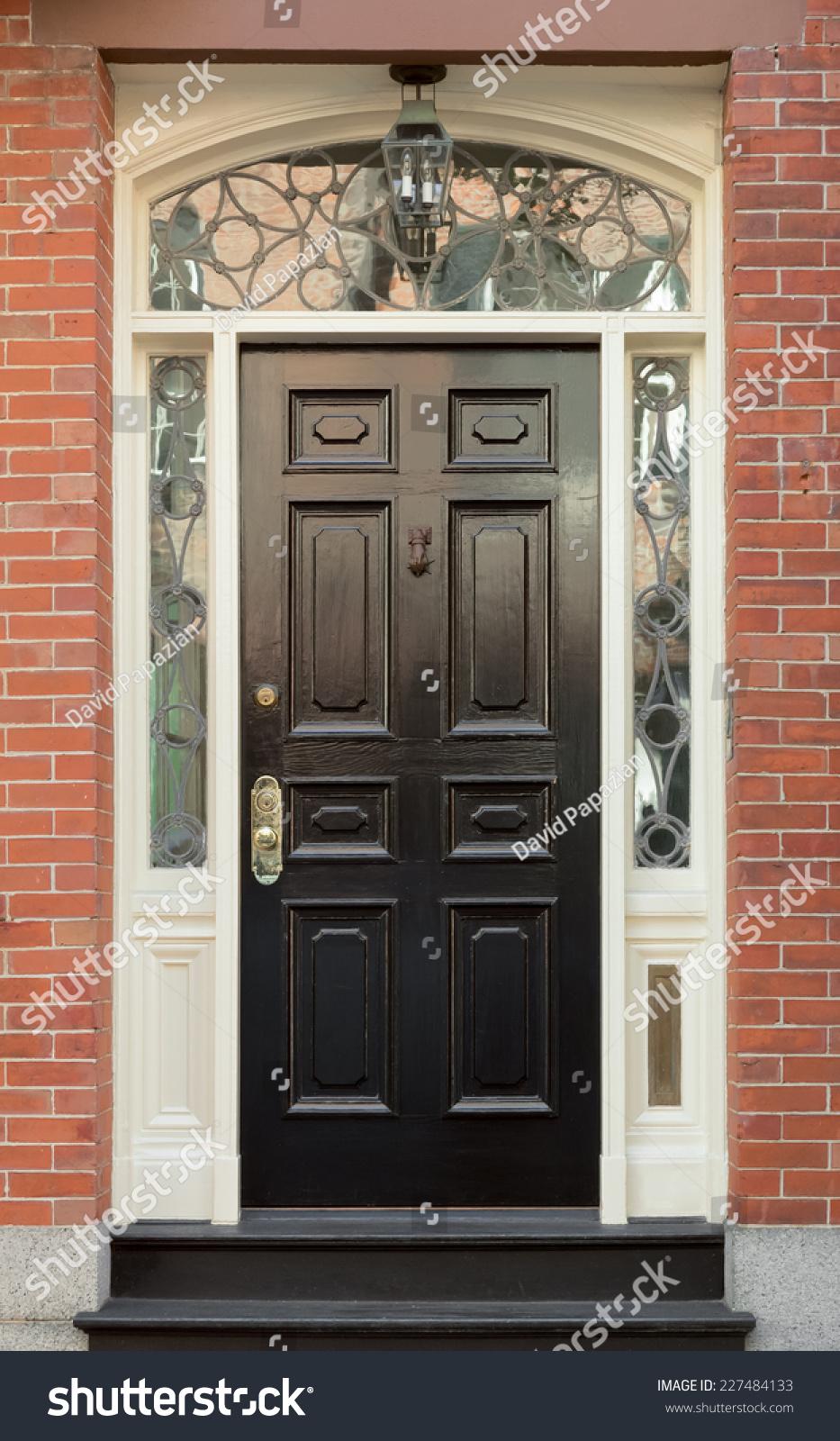black front door and surrounding white door frame with ornate windows in brick building