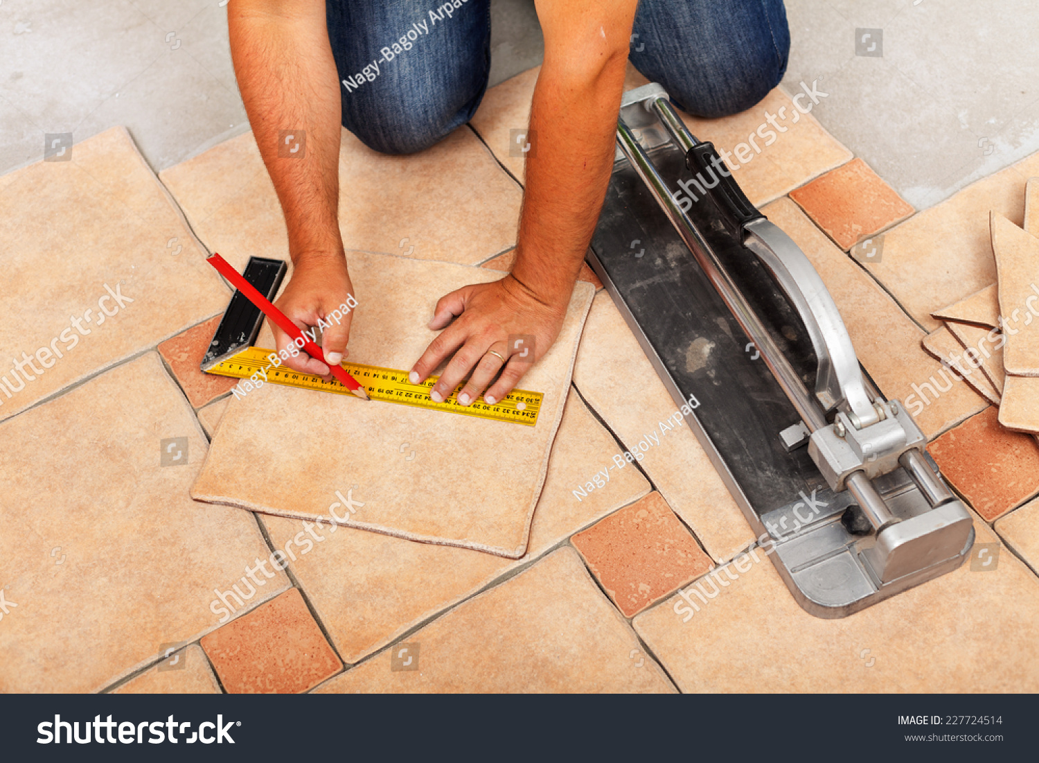 Installing ceramic floor tiles measuring cutting stock photo installing ceramic floor tiles measuring and cutting the pieces closeup dailygadgetfo Image collections