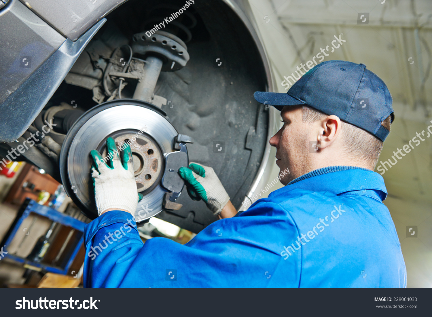 Car mechanic worker replacing brakes lifted stock photo for Garage fix auto nimes