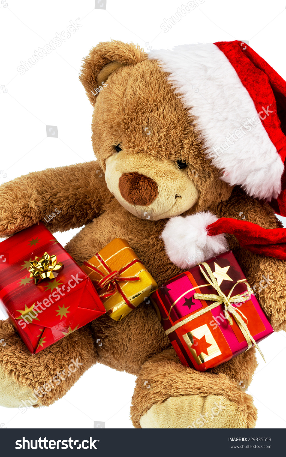 A teddy bear with gifts for christmas dressed as santa