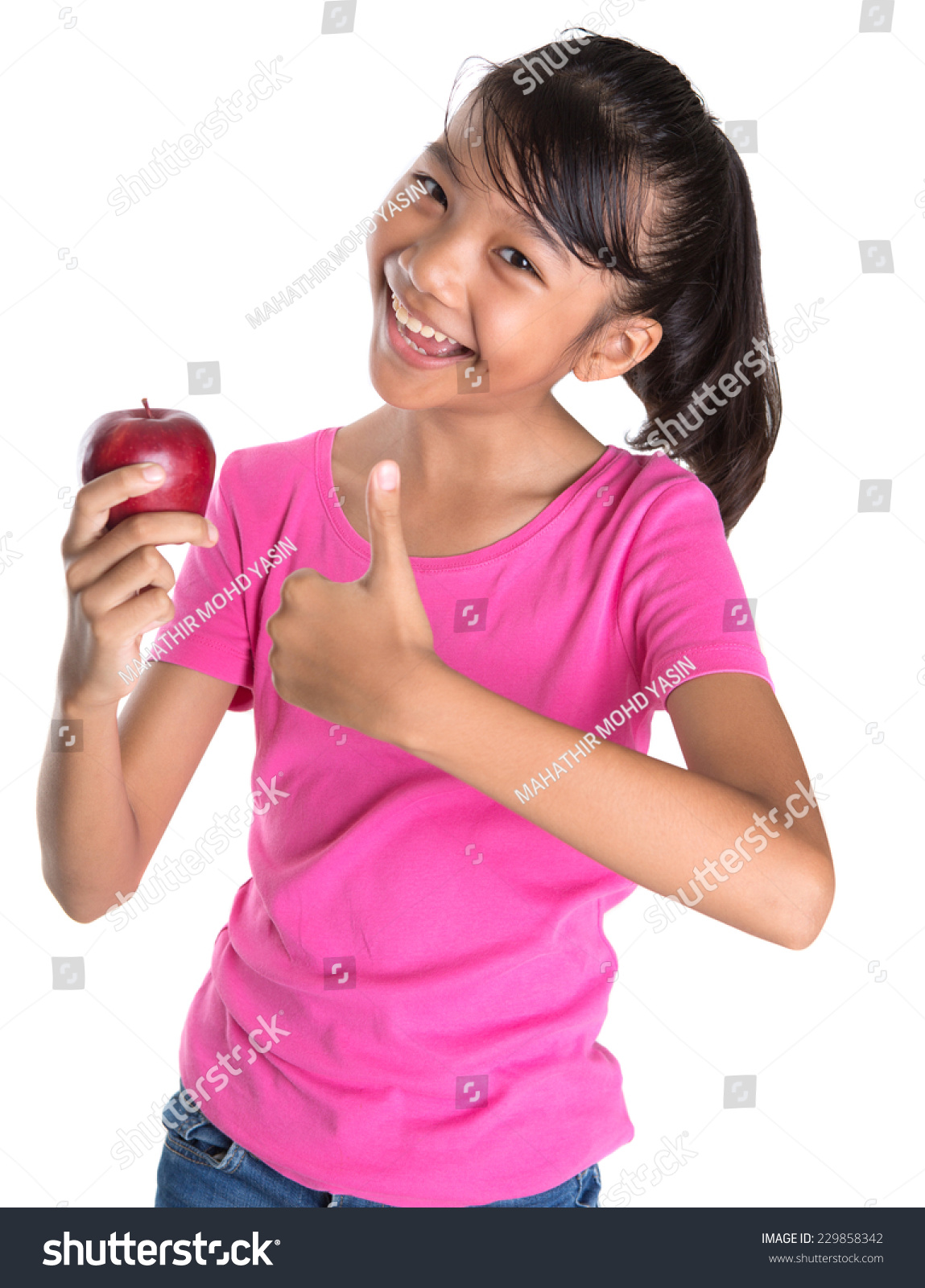 Young Asian Malay teen showing a thumbs up sign with a red apple over white  background
