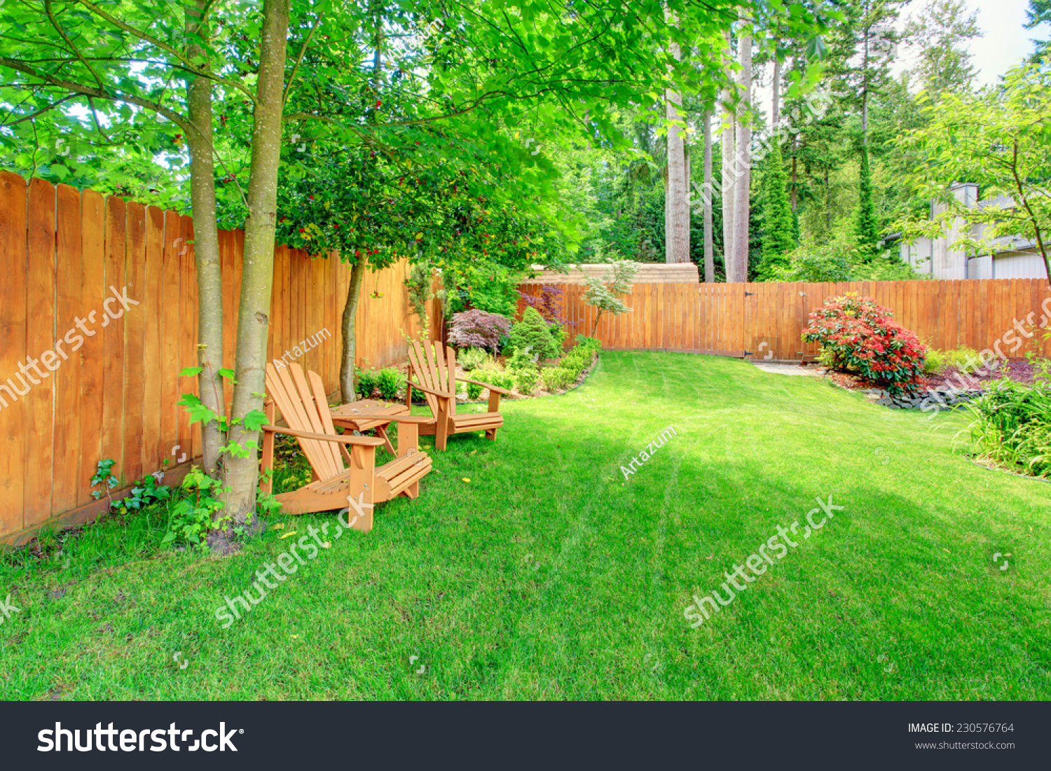 fenced backyard with green lawn flower beds and romantic