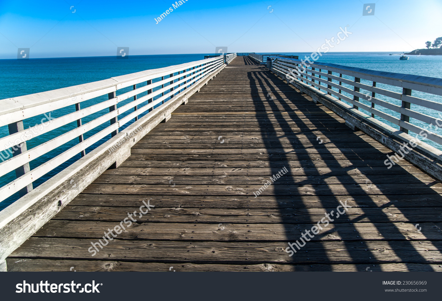 The historic wooden pier at San Simeon reaches into the blue Pacific Ocean