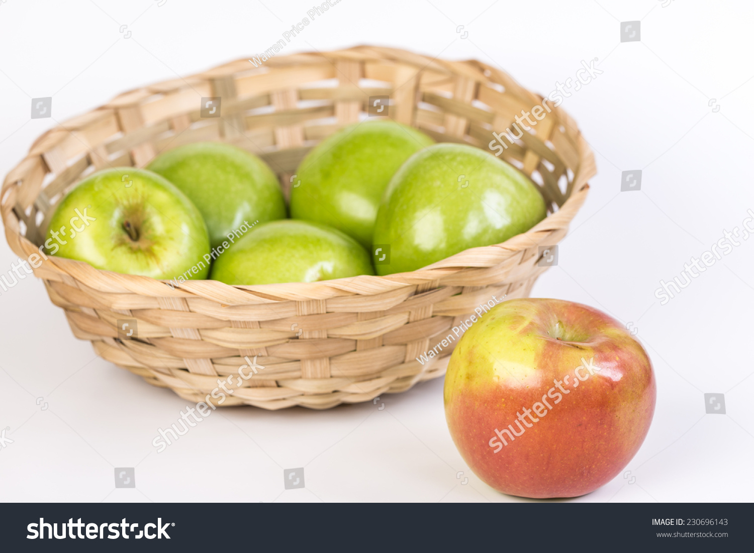 green and red apples in basket. green apples in basket with red apple outside, alone. conceptually, ostracized due to and p