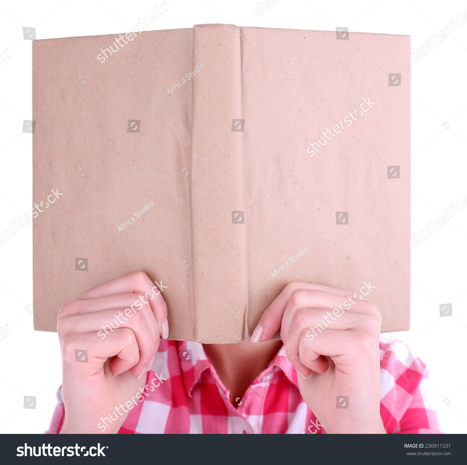 Book Covering Face : Girl reading book covering her face isolated on white