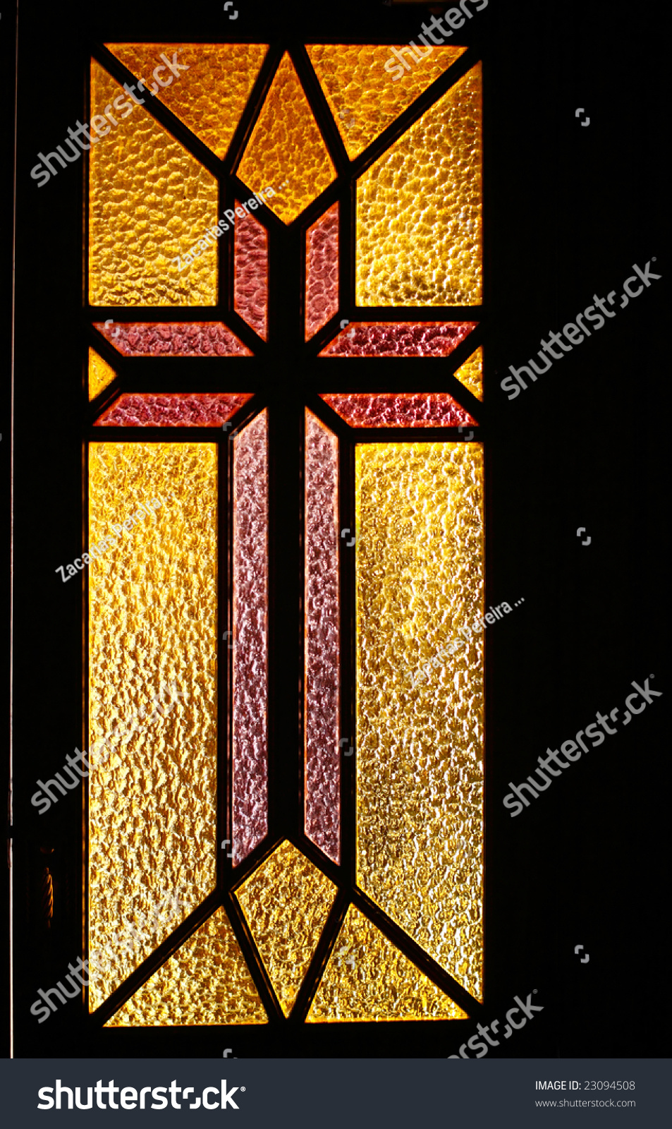 simple stained glass window in a door of a catholic church