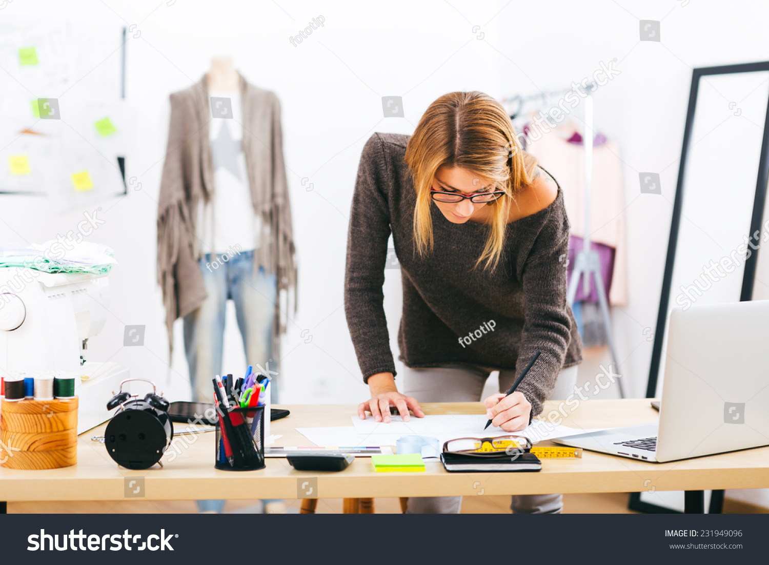 Young attractive female fashion designer leaning on office desk working with a laptop at home for Work from home fashion design jobs