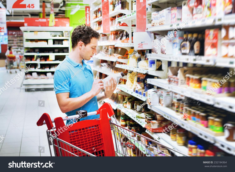 man reading label on bottle supermarket stock photo (edit now