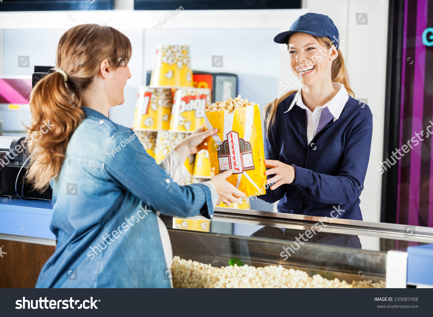 happy female seller giving popcorn paperbag stock photo  happy female seller giving popcorn paperbag to pregnant w at cinema concession stand