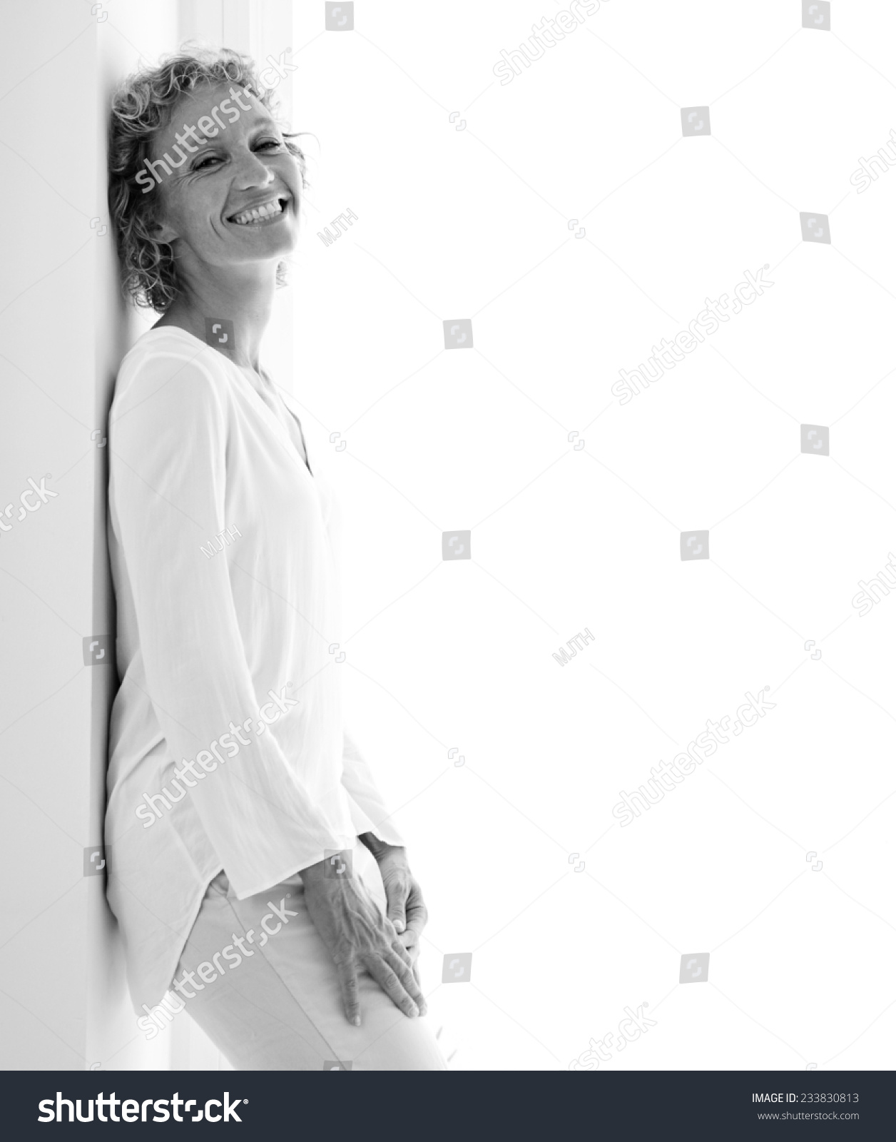 Black and white portrait of a smart professional business woman smiling and leaning on a wall