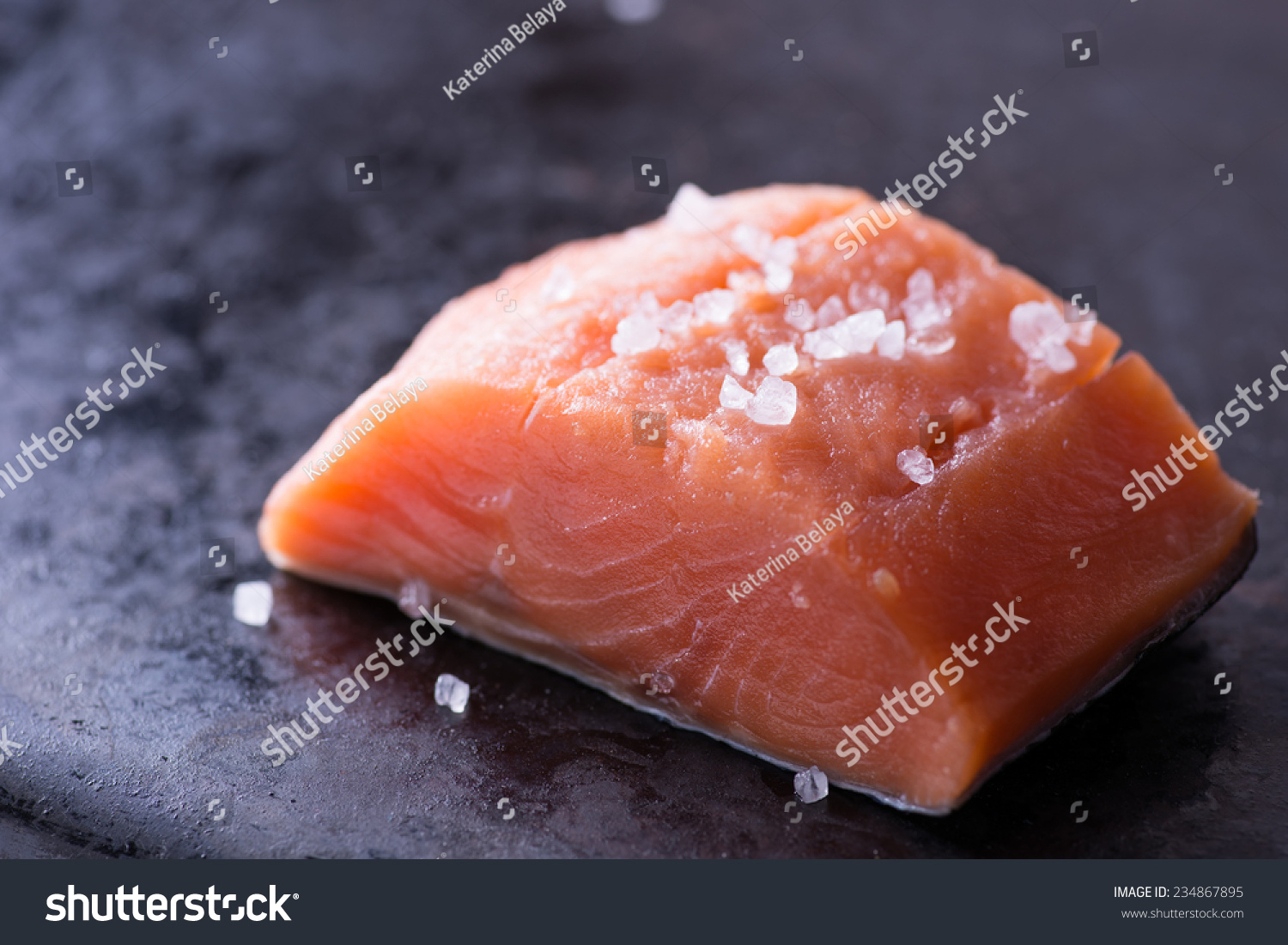 Raw red fish fillet with sea salt on dark pan close up for Red fish fillet
