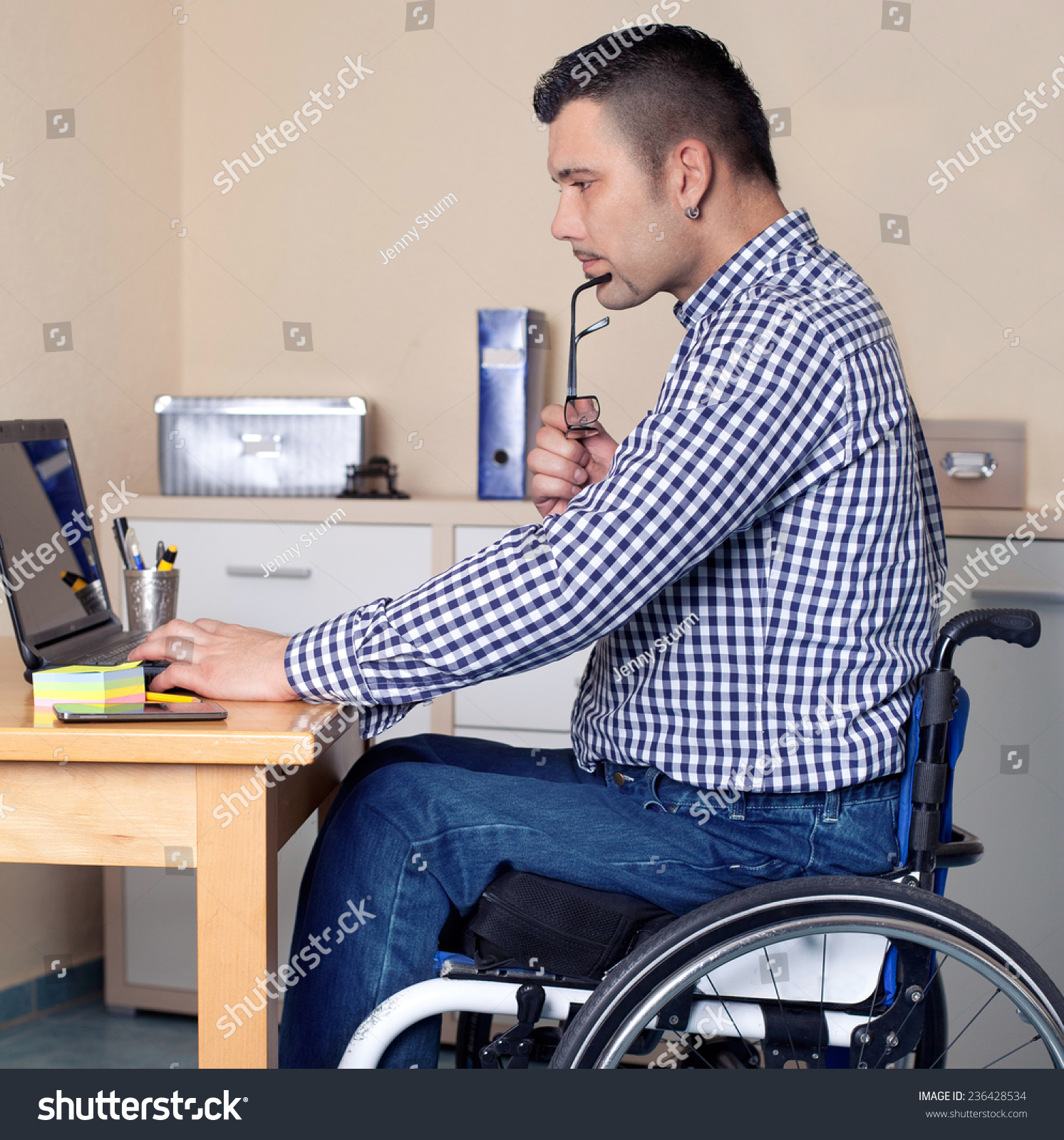 Man In Wheel Chair - Young man in wheelchair in office is using his laptop disabled young man is surfing