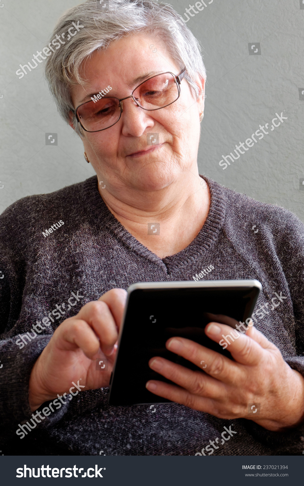 88cf952ea5 Happy Elderly woman using a tablet and smiling. Grandma Using Tablet PC in  Living Room