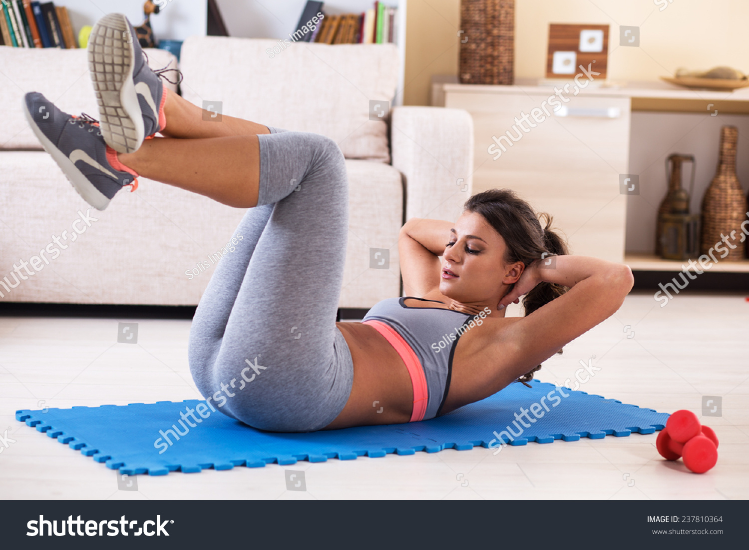 Attractive Female Doing Exercise In Her Living RoomShe AbsWorkout