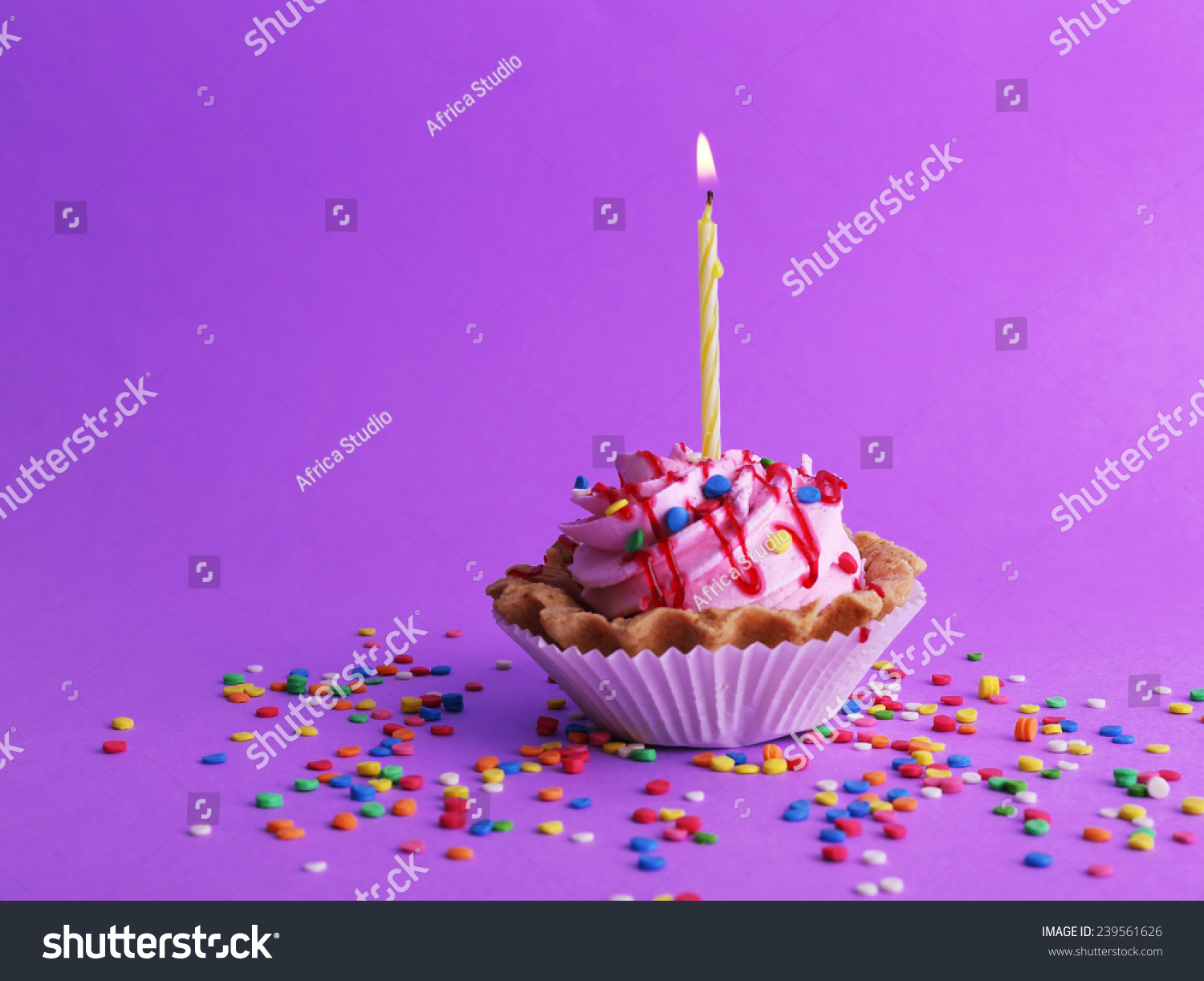 Birthday Cup Cake With Candle And Colorful Sparkles On Purple Background