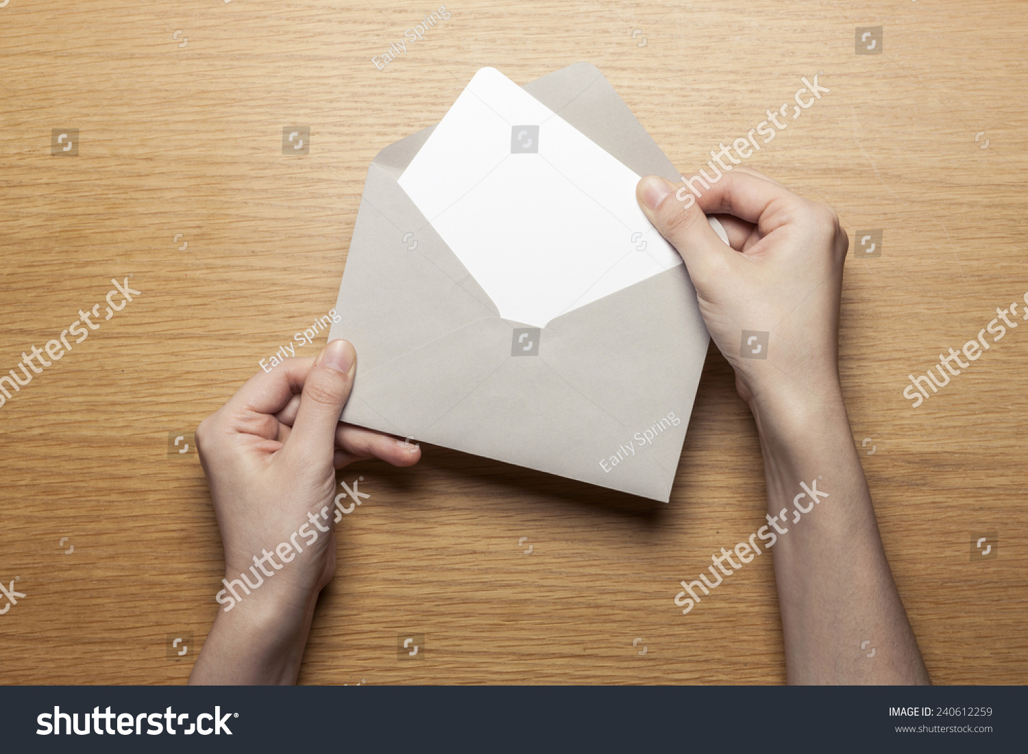 A female(woman) hand hold(open) a envelope and post card on the wood desk, top view at the studio.  #240612259