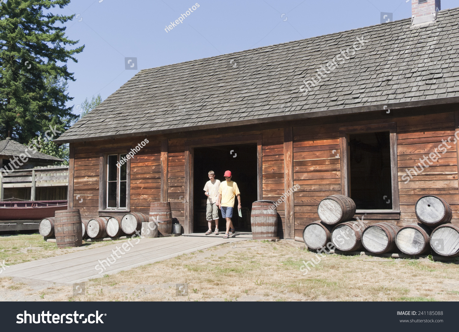Log Cabin With Tourists And Barrels Rural Scenery In