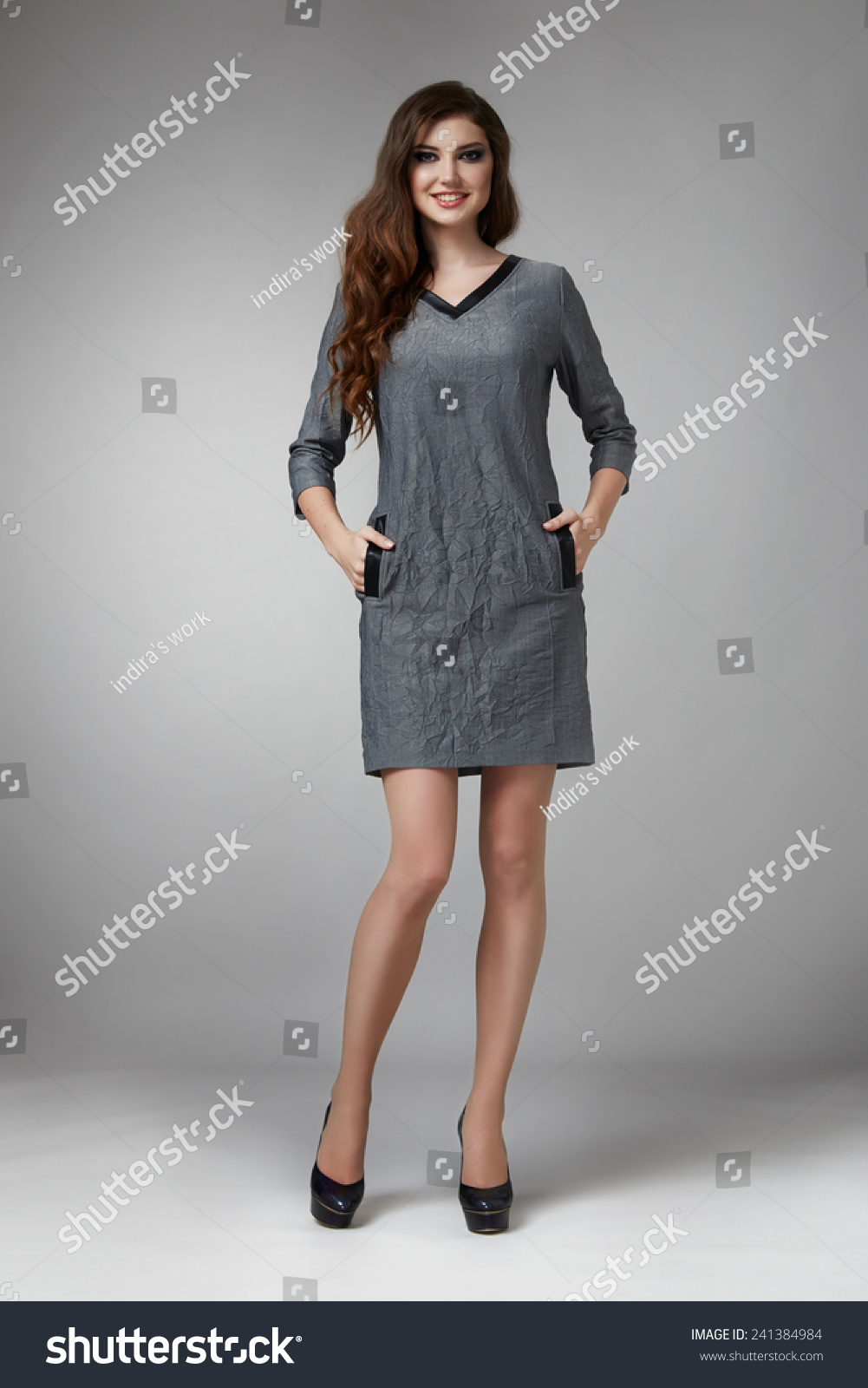 bbd172c752c Beautiful sexy young business woman with evening make-up and long brown hair  wearing a small gray dress and high-heeled black shoes