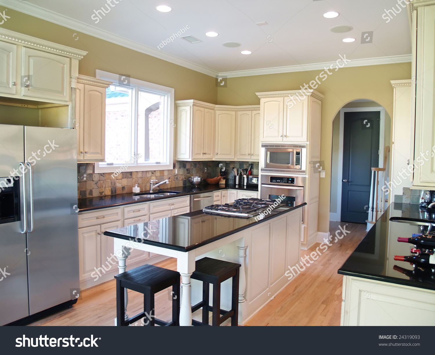 A Modern Kitchen With White Cabinets And Black Granite