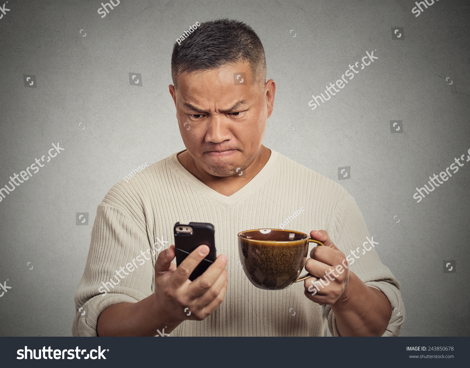 Frustrated office worker on the phone holding stock photo image - Closeup Portrait Worried Angry Frustrated Man Reading Bad News Sms On Smart Mobile Phone Drinking Holding