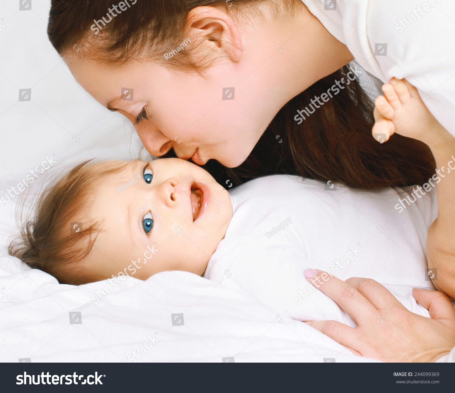 Baby bed next to mom - Mom Kissing Little Baby On The Bed At Home
