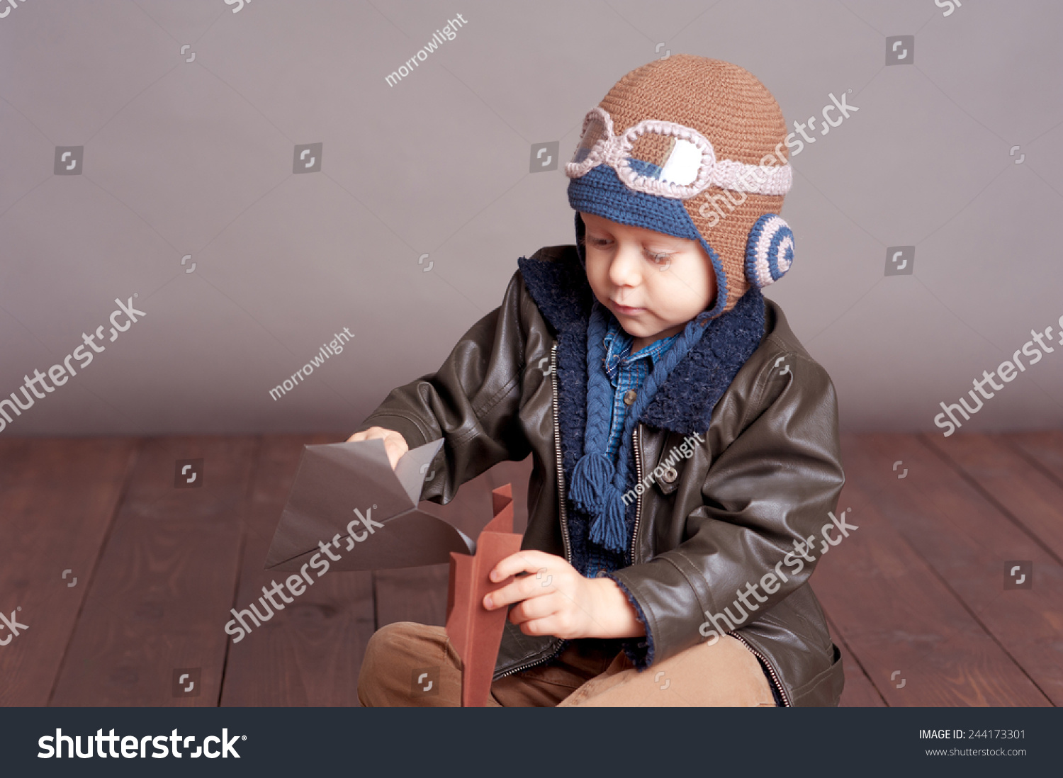 9b0168067f5 Cute baby boy wearing stylish leather jacket and aviator cap over gray.  Playing with paper