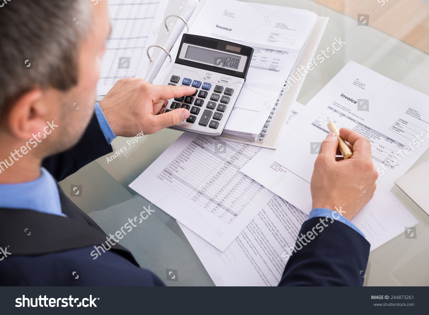 over shoulder view businessman calculating invoices stock photo over the shoulder view of businessman calculating invoices using calculator
