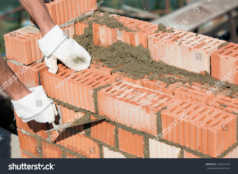 Caulking Concrete Walls : Bricklayer worker installing red blocks caulking stock