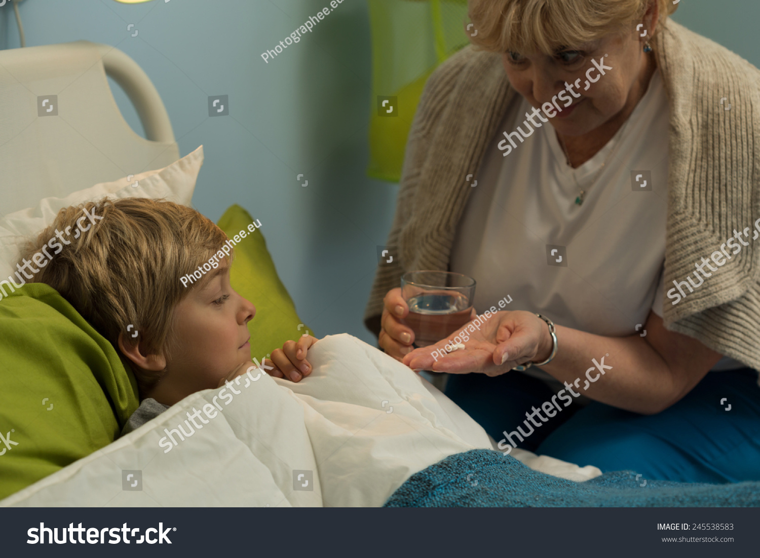 granny boy Caring granny giving the medicine to sick little boy