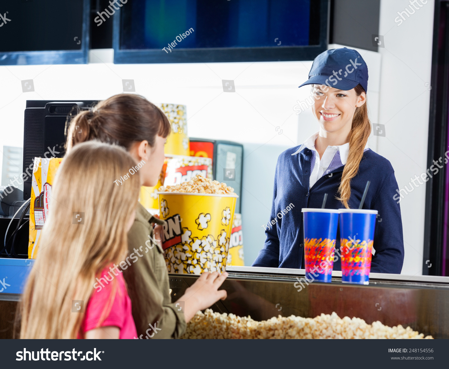 little girls buying popcorn drinks female stock photo  little girls buying popcorn and drinks from female seller at cinema concession stand