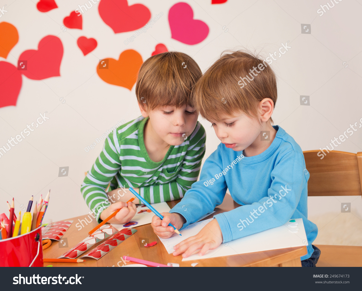 kids children doing valentines day arts and crafts with hearts pencils paper