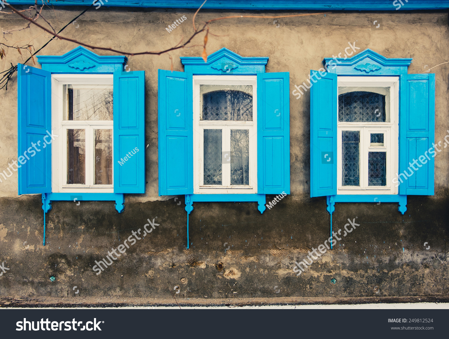 Three old wooden window in a wall covered with cement toned image in Astrakhan, Russia. Vintage color.