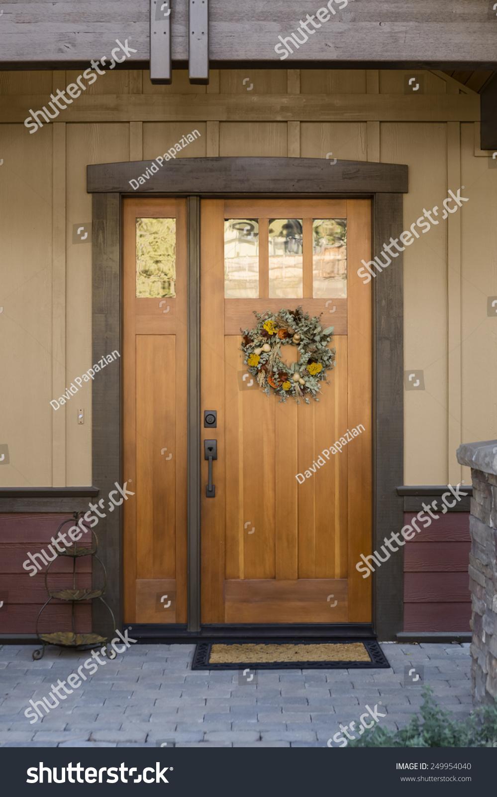 Warm Entryway With Natural Wood Front Door, Hanging Wreath, Doormat And  Decorative Piece On