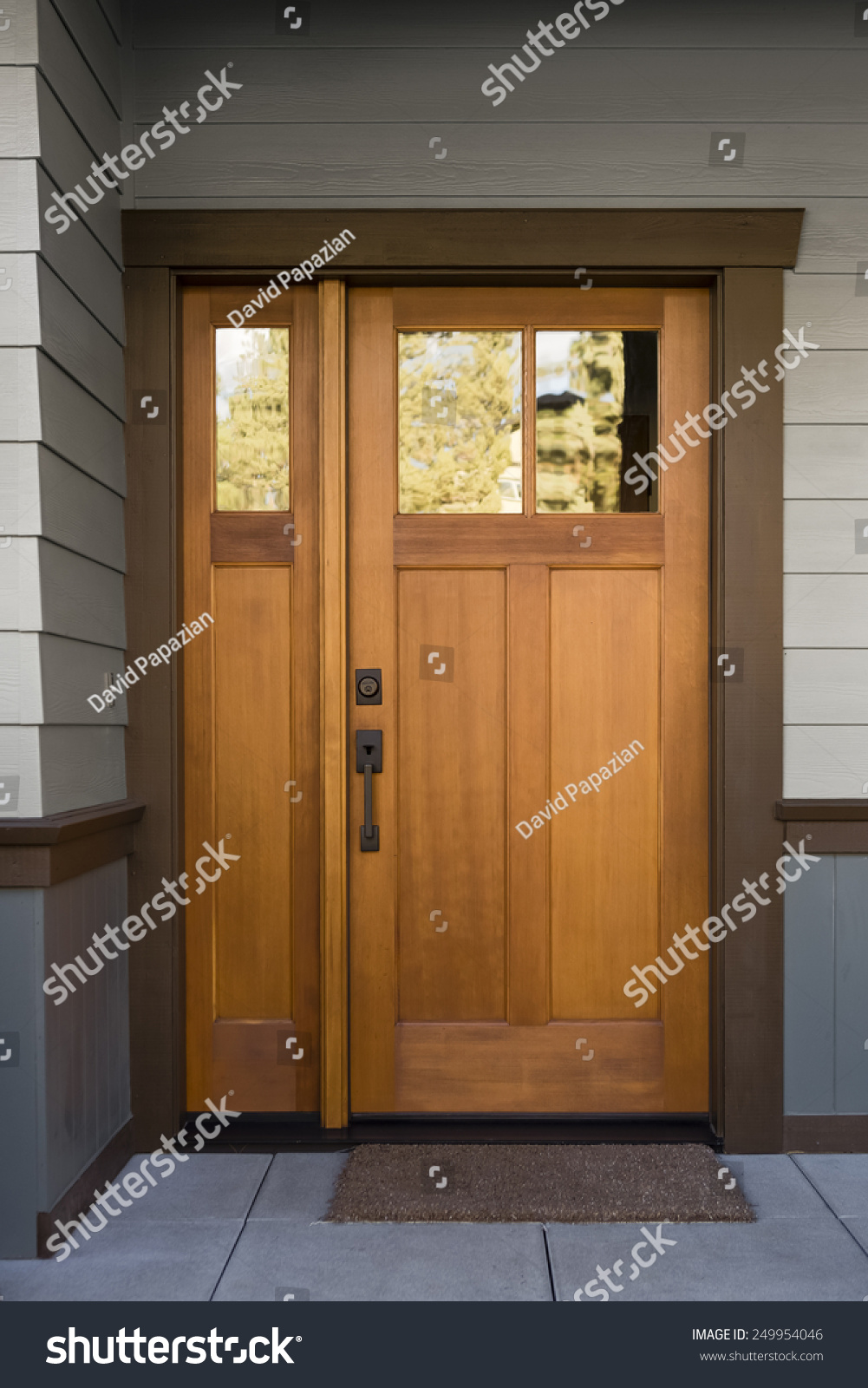 Natural wood front door on grey and blue siding exterior for Natural wood front door