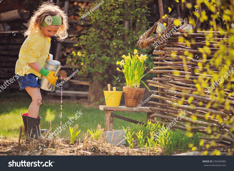 Child Girl Yellow Cardigan Watering Flowers Stock Photo (Royalty ...