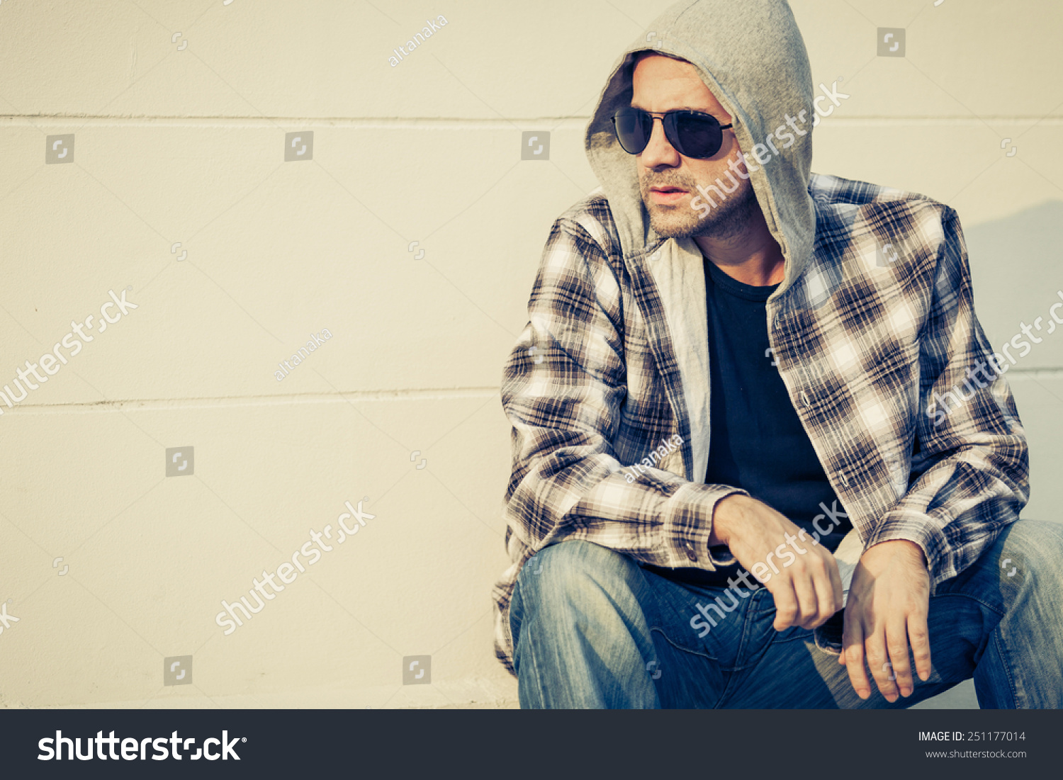 cb86e96d50a3 Portrait of a one sad man in sunglasses sitting outdoors near the house at  the day