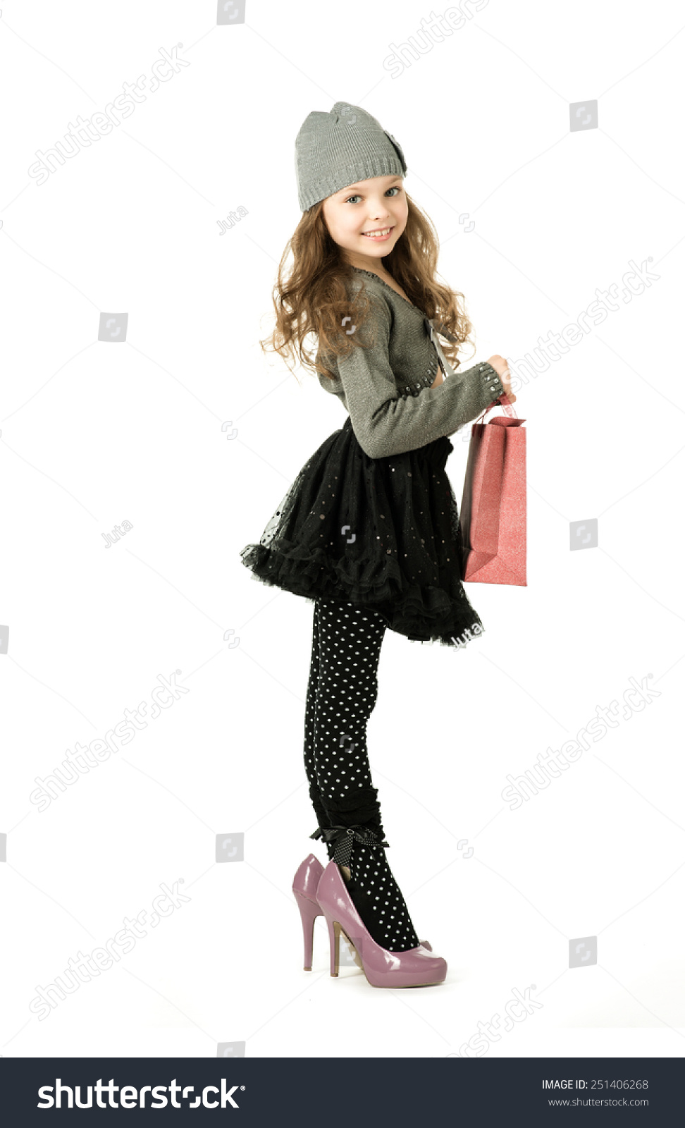 fashionable little girl in her mothers shoes playing