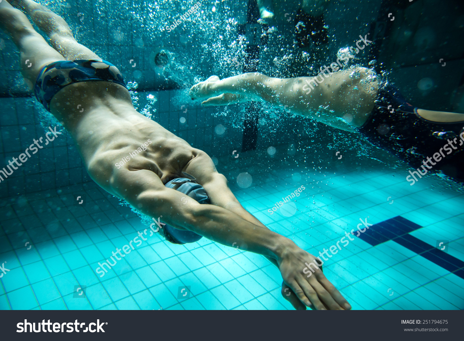 two swimmers swimming poolunderwater photo stock photo