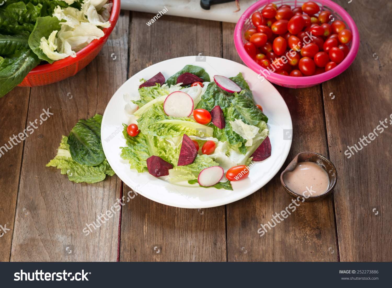 Fresh salad with tomatoes and beetroot on wood table stock