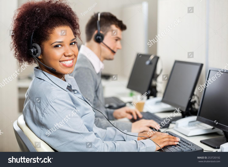portrait smiling female customer service representative stock portrait of smiling female customer service representative male colleague working in office
