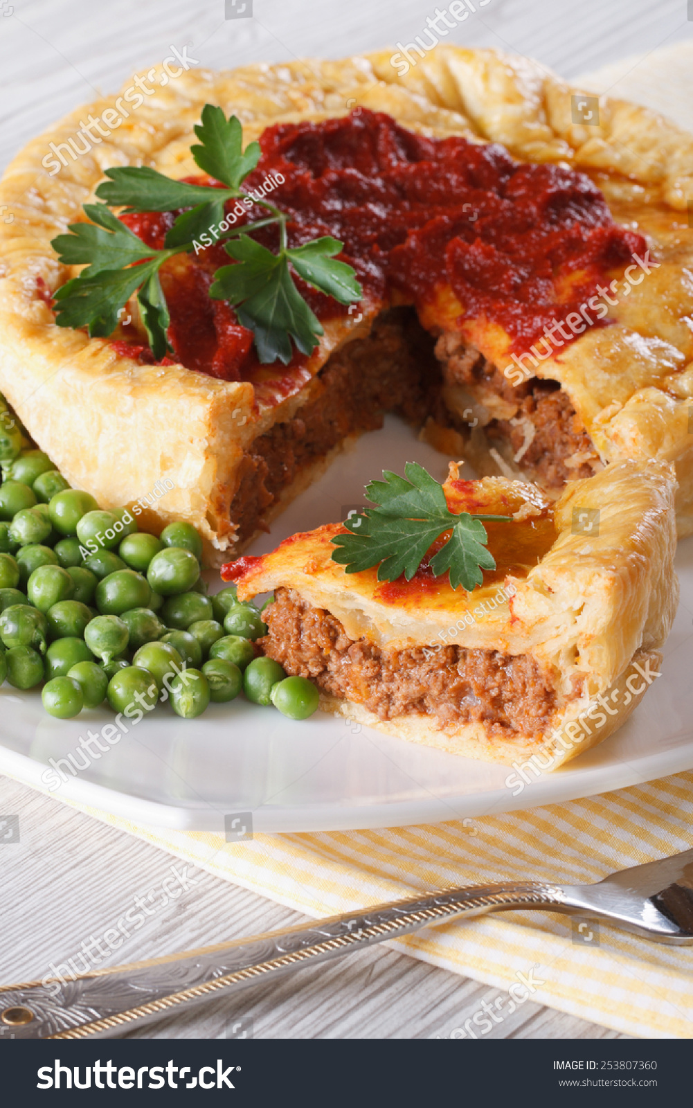 Pieces of meat pie and a garnish of green peas on a plate. Vertical close & Pieces Meat Pie Garnish Green Peas Stock Photo (100% Legal ...