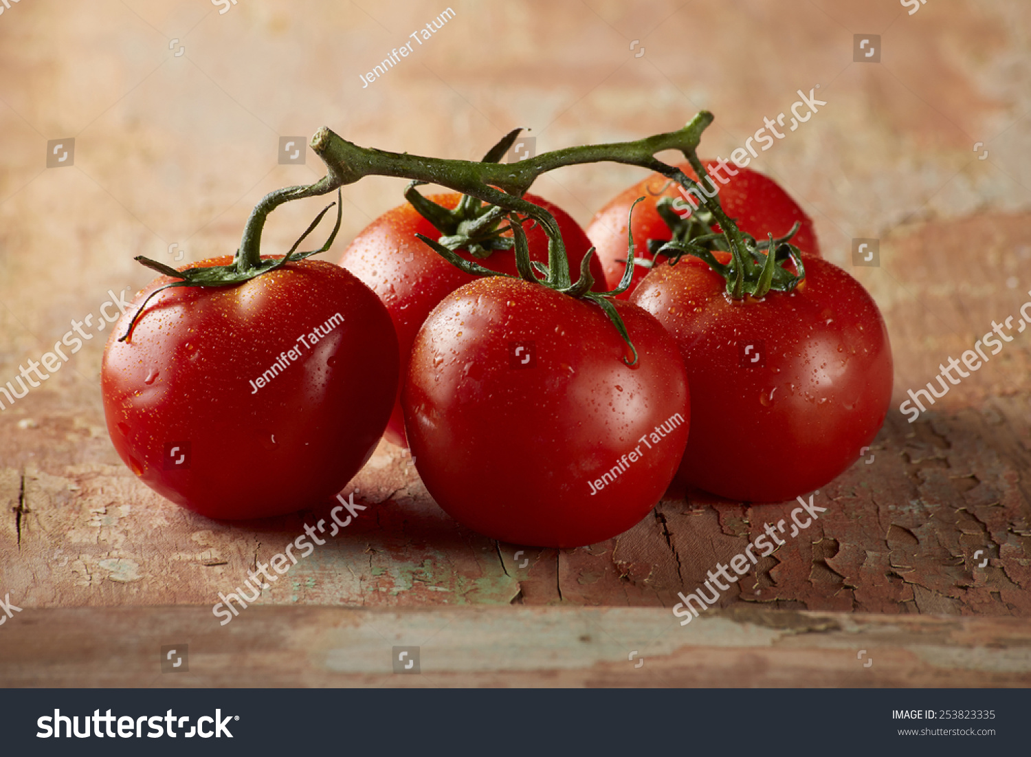 Tomatoes on vine with wood background stock photo