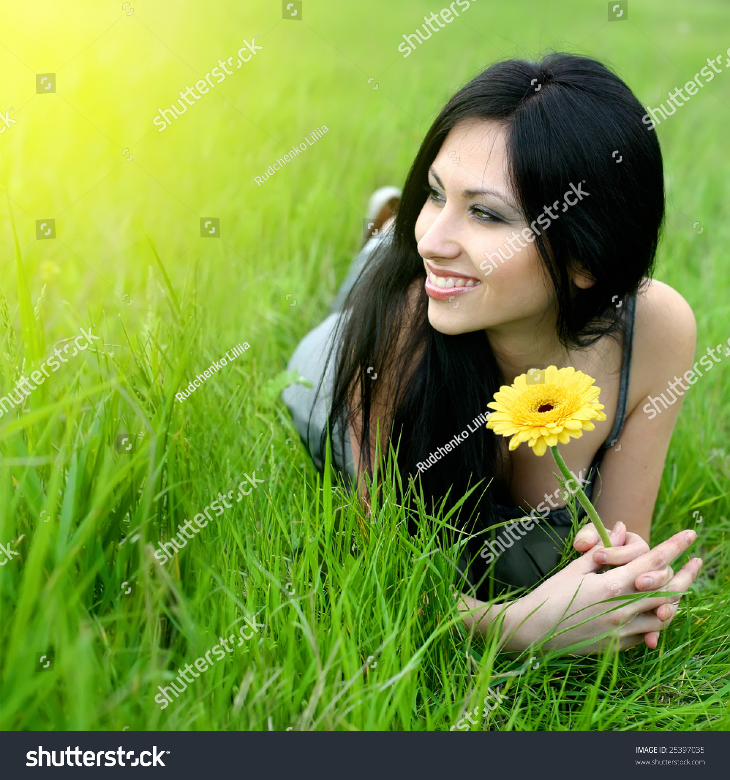 Beautiful Young Woman Relaxing In The Grass Stock Photo