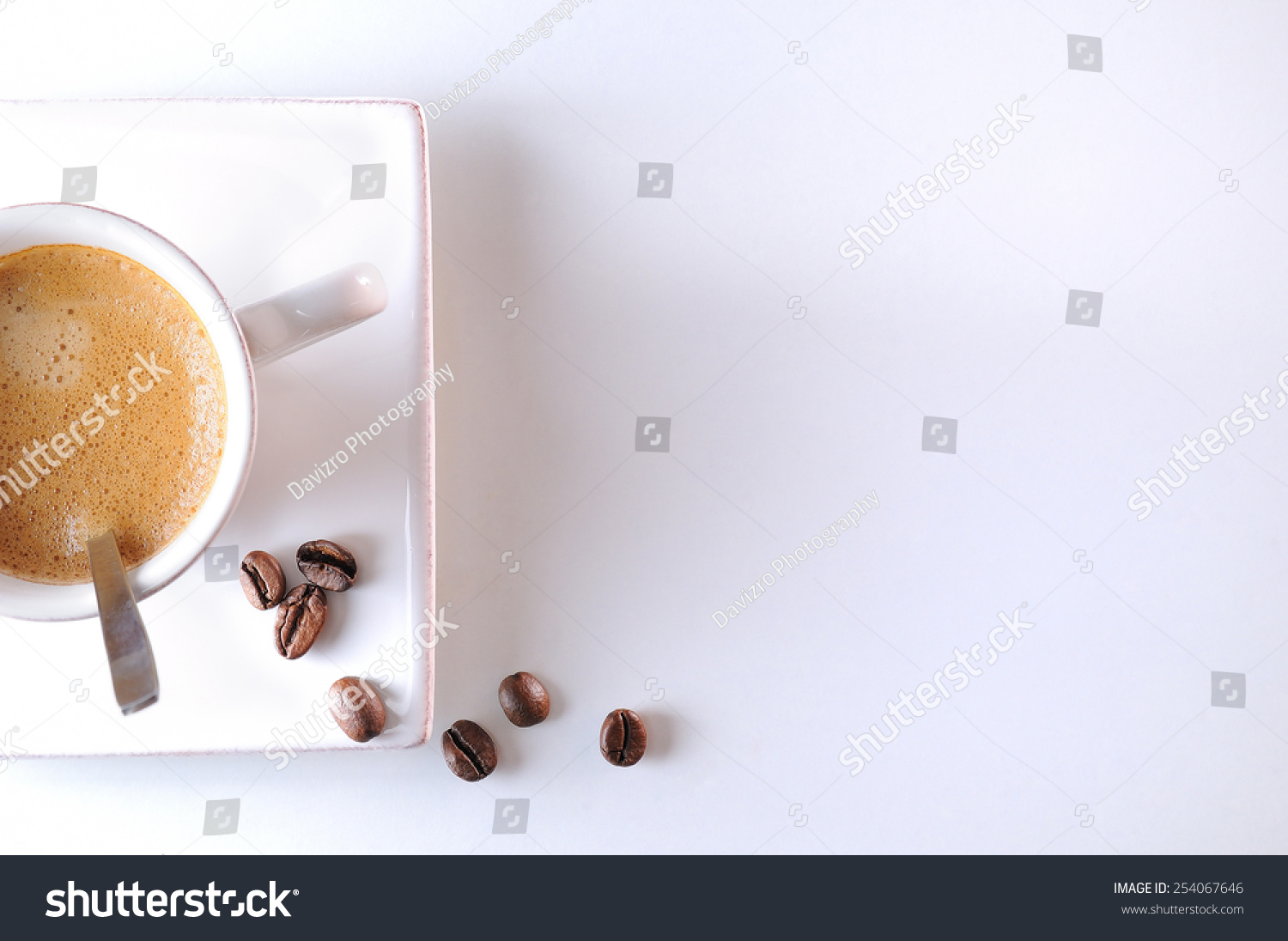 Cup With Spoon And Coffee Beans On A White Table Top View Stock Photo