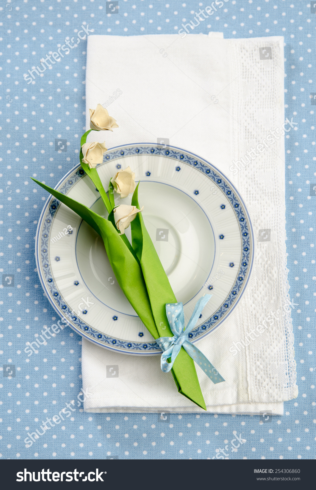 Festive table decoration flowers origami lily stock photo royalty festive table decoration flowers origami lily of the valley on a saucer blue tablecloth with white izmirmasajfo