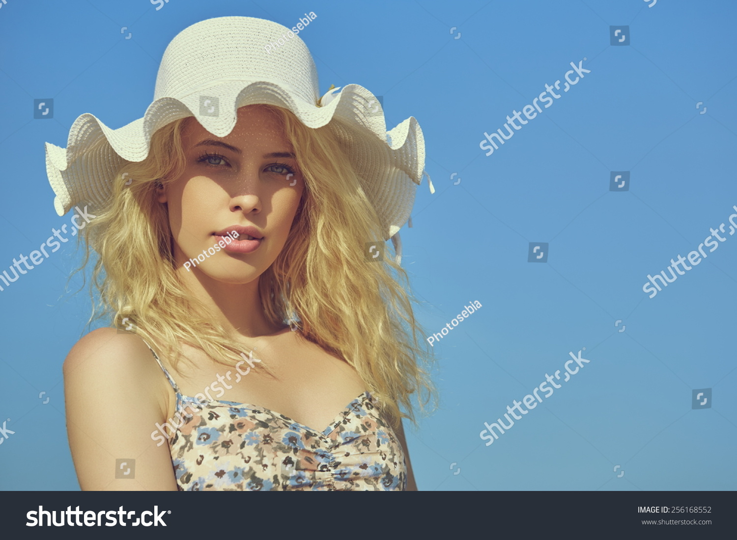 Portrait of beautiful young lady with long blond curly hair and blue eyes wearing  white sun hat with wavy brim over clear blue sky. Copy space. - Image 7fc3c88f9d3b